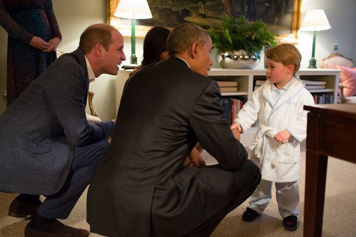The President greets Prince George, who is in a bath robe.