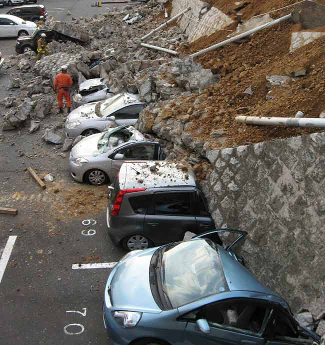 Vehicles are crushed by a collapsed wall at a carpark in Mito city in Ibaraki prefecture.
