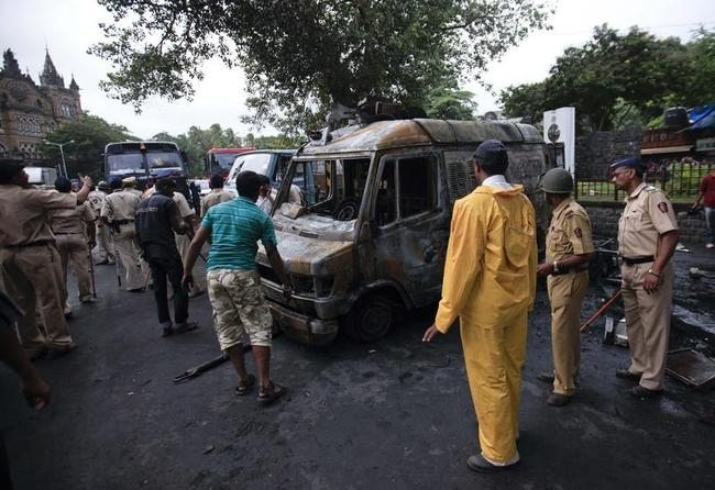 Policemen stand near a burnt vehicle after a protest turned violent in Mumbai