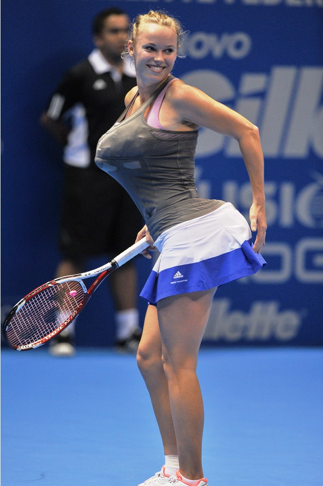 Danish tennis player Caroline Wozniacki impersonates Serena Williams by carrying towels under her clothes simulating bigger breasts and bottom, during an exhibition match against Maria Sharapova of Russia at the Ibirapuera Gymnasium in Sao Paulo, Brazil, on December 7. (Photo: AFP)