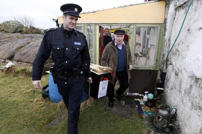 Presiding officer Hugh O'Donnell and police (Gardai) officer Ronan McNamara remove the ballot box after votes were cast on the island of Inishfree Ireland