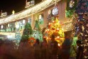 People walk past Christmas trees made of recyclable materials displayed at a city hall complex in Manila