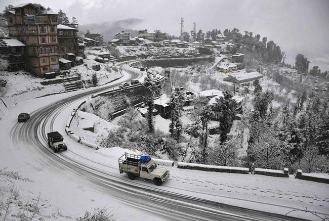 Vehicles drive down a snow-covered road after heavy snowfall in Shimla