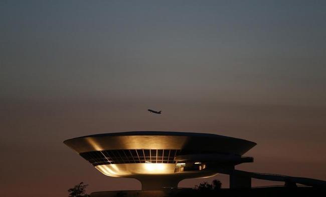 A plane flies over the Contemporary Art Museum designed by architect Niemeyer in Niteroi city near Rio de Janeiro