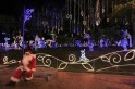 A man dressed as Santa Claus sits on bench in Usaquen Park during Festival de Navidad celebrations in Bogota