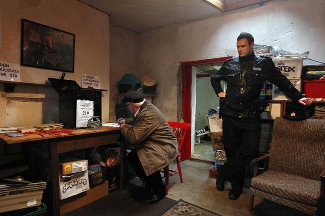 Presiding officer Hugh O'Donnell prepares the ballot box as Gardai Ronan McNamara watches on the island of Inishfree Ireland