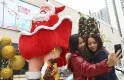 Women take pictures in front of a Santa Claus figure outside a shopping mall ahead of Christmas in Dongguan