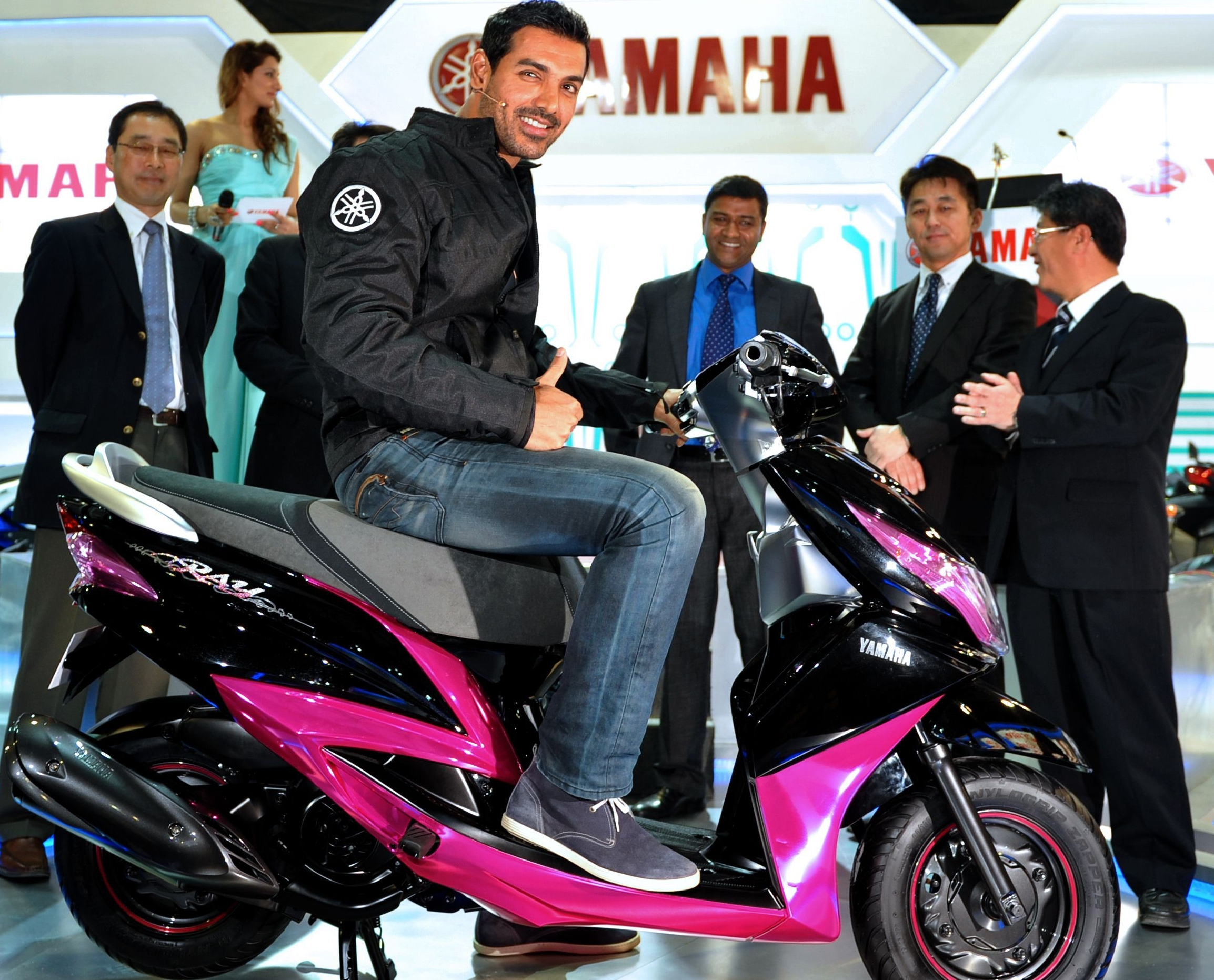 John Abraham sits on a newly launched scooter as he poses with Yamaha representatives during the 2012 India Auto Expo in New Delhi.