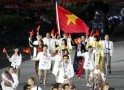 Vietnam's flag bearer Nhat holds the national flag as he leads the contingent in the athletes parade during the opening ceremony of the London 2012 Olympic Games at the Olympic Stadium