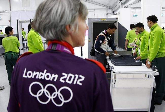 Indian shooting team member Sanjeev Rajput holds his laptop as he goes through a security check at the Welcome Center near the Athletes