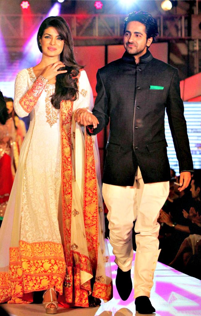 Bollywood actors Priyanka Chopra and Ayushmann Khuranna display designer Manish Malhotra's creation during a fashion show to support the cancer patients in Mumbai.