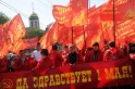 Russian communist party supporters carry red flags and poster reading