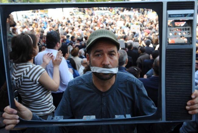 A Tunisian journalist holds a tv frame