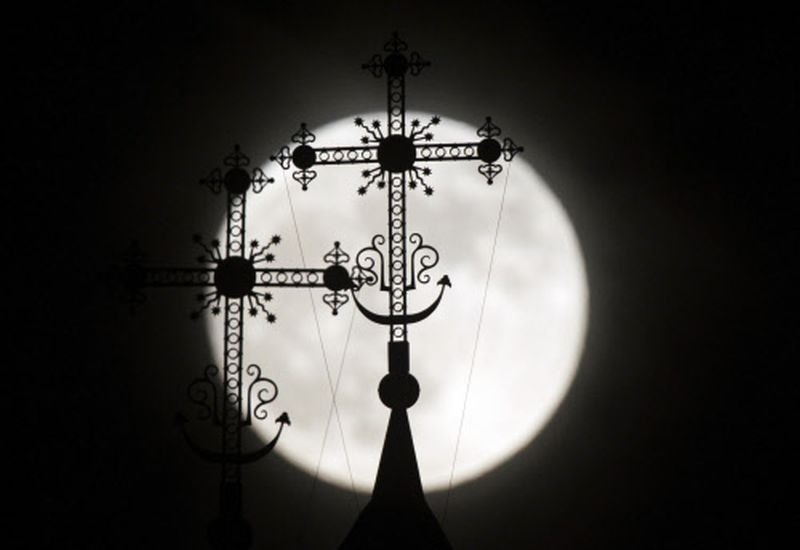 The  full moon rises behind a steeple with crosses of an Orthodox church in  the town of Novogrudok, 150 km west of Minsk, Belarus