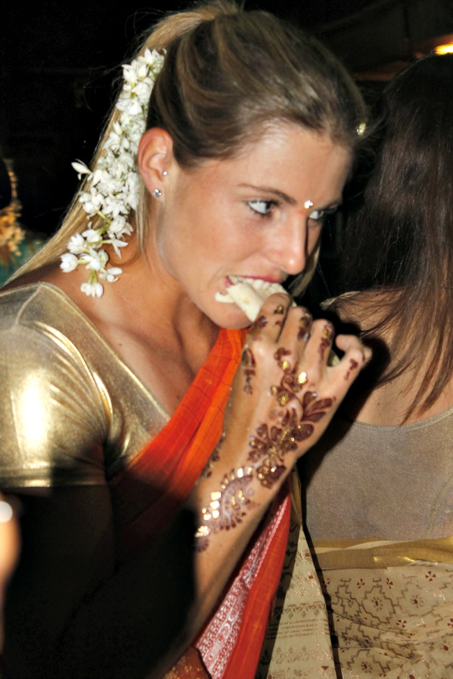 One foreign player grabs a bite of Indian food.