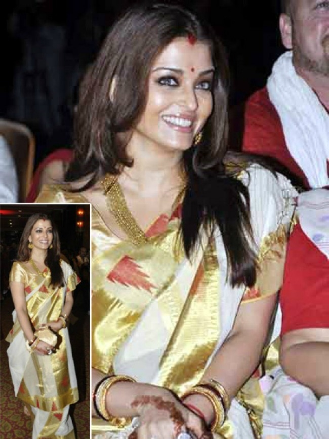 Traditional chic: This Durga Puja, get inspired by Aishwarya Rai's beautiful sari draped the Bengali way. The rich yet simple white and gold border Ikkat sari is a fine example of the lively festive season, and reminds us of the traditional Bengali woman who have mastered the drape over generations. A must try we say!