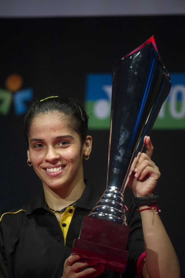 Olympic bronze-medallist shuttler Saina Nehwal fought through a troubling knee to clinch her fourth title of the year by lifting the Denmark Open Super Series Premier trophy with a dominating win in the final on Sunday.