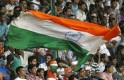 A fan of India's cricket team waves an Indian national flag in the stands during the fourth day of their second test cricket match against New Zealand in Bangalore