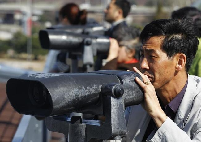 South Koreans look north through binoculars near the demilitarized zone separating North Korea from South Korea in Paju