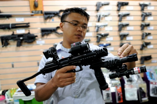 A sales man at a practical defence and weapons shop in Manila, demonstrates how to use a conversion kit that transforms a 9 mm hand gun to resemble a close quarter submachine gun unit. Photo: AFP
