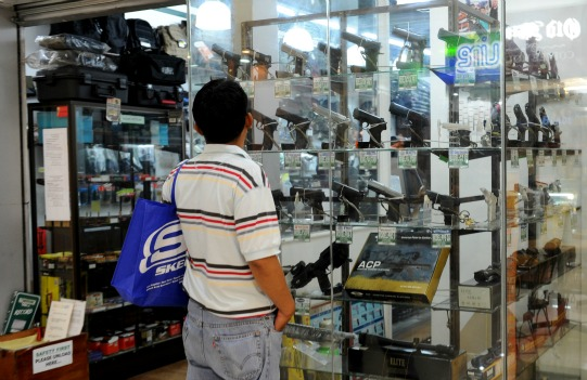 A gun enthusiast looks at a showcase of guns shop in Manila. Photo: AFP
