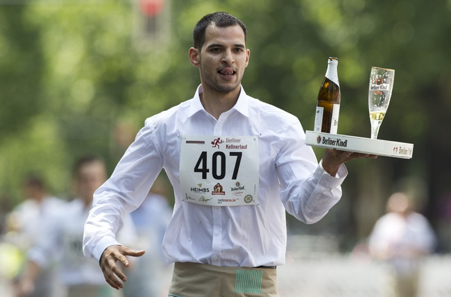 A contestant carries a tray with a filled beer glass as he takes part in the annual
