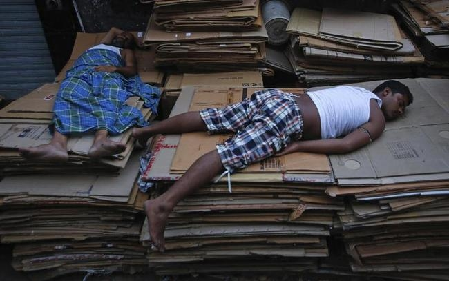 Labourers sleep on empty cardboard cartons outside a warehouse in Mumbai