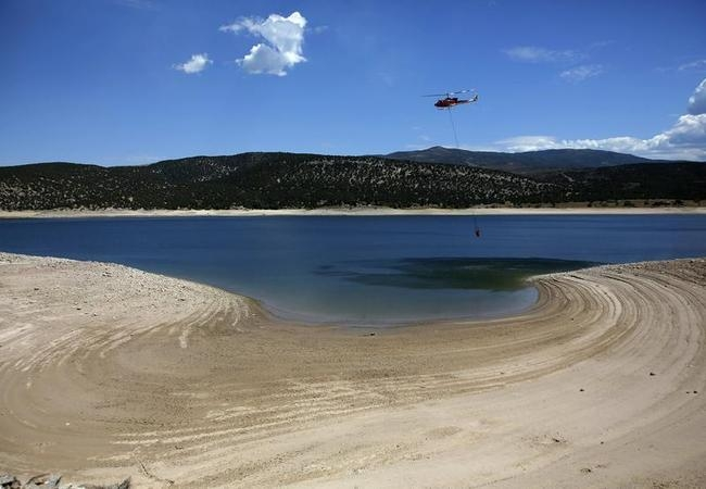 Helicopter fills a bucket of water for use in fighting the Rockport Fire near Rockport State Park in Utah