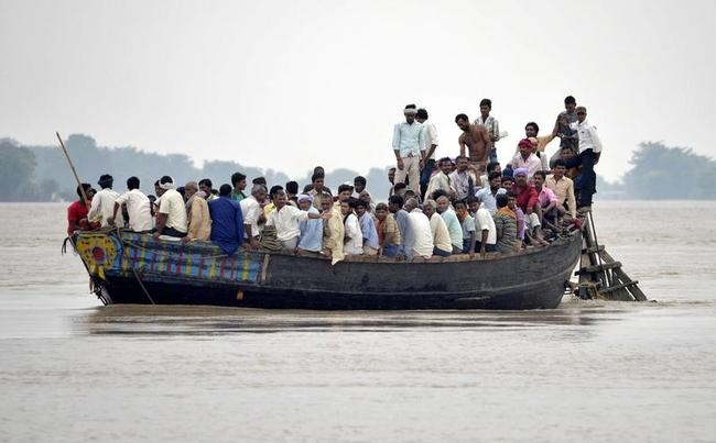 Flood-affected villagers use a boat as they navigate through floodwaters after heavy rains at Patna district