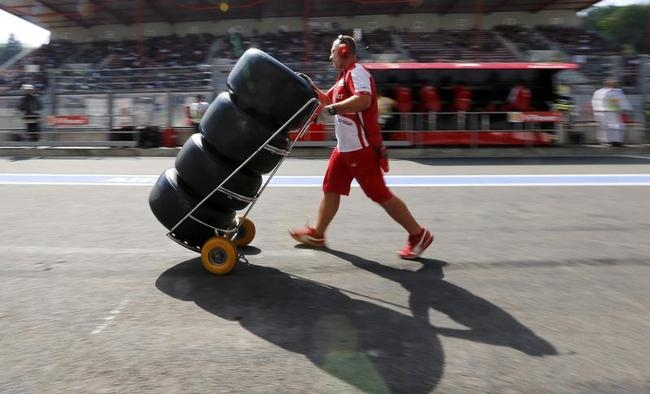 A Ferrari Formula One technician pushes a trolley with Pirelli tyres during the second practice session of the Belgian F1 Grand Prix in Spa Francorchamps