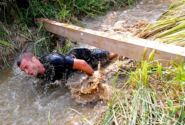 A competitor crawls through mud water during the Fighters' Run competition in Zanka, Hungary. (Photo: Reuters)