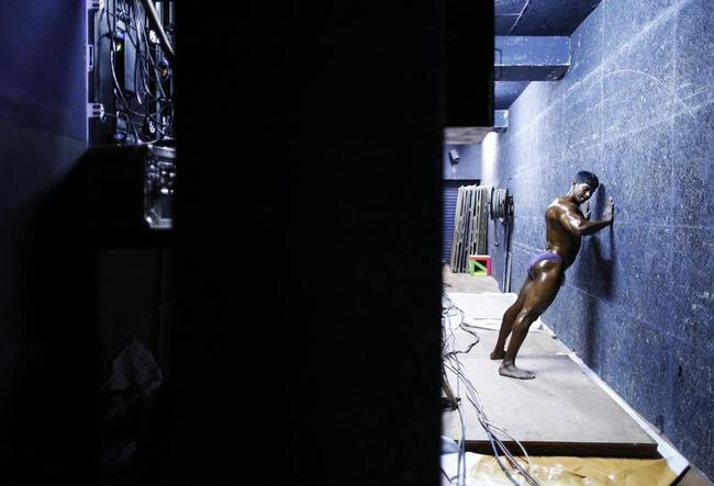 A competitor warms up backstage during a bodybuilding competition in Mumbai