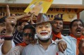 A supporter wearing a mask of Narendra Modi celebrates outside the party's headquarters in the western Indian city of Ahmedabad