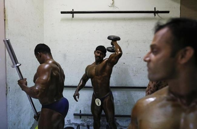 Competitors warm up backstage during a bodybuilding competition in Mumbai