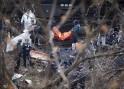 Officials remove a body from the scene of a Metro North train derailment in the Bronx borough of New York