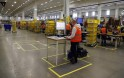 Worker supervises items for delivery from warehouse floor at Amazon's new distribution center in Brieselang