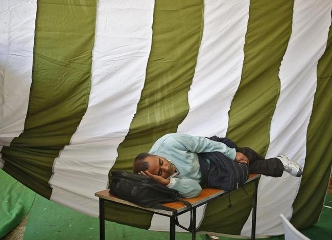 A polling officer takes a nap at an election training centre on the eve of state election in New Delhi