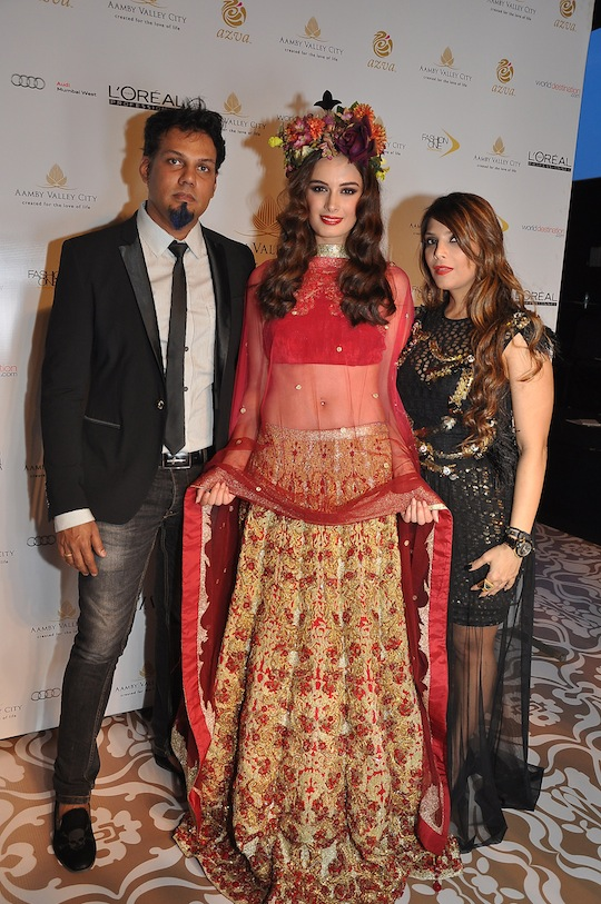 Evelyn Sharma in a bright red lehenga encrusted with gold, teamed with a sexy matching velvet choli and pink net dupatta.