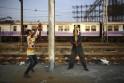 Boys play cricket along the tracks as a suburban train passes by near Bandra railway station in Mumbai