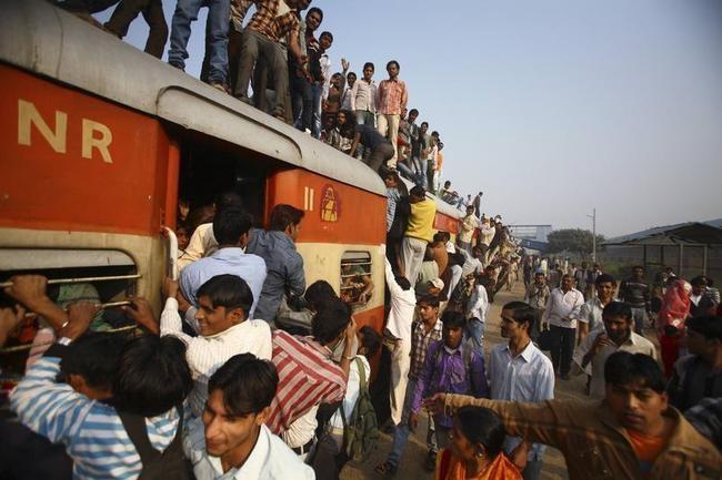 Commuters struggle to board a train at Noli railway station in Uttar Pradesh