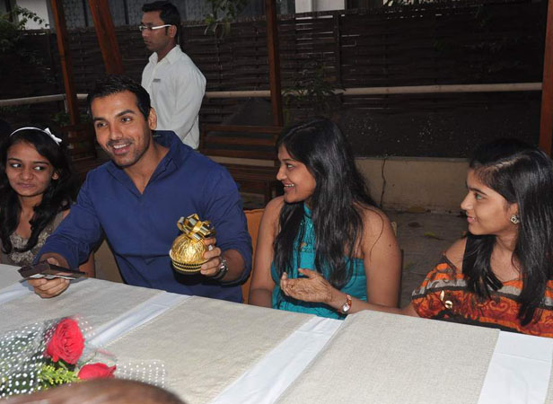 John Abraham accepts a gift from his female journalist fans