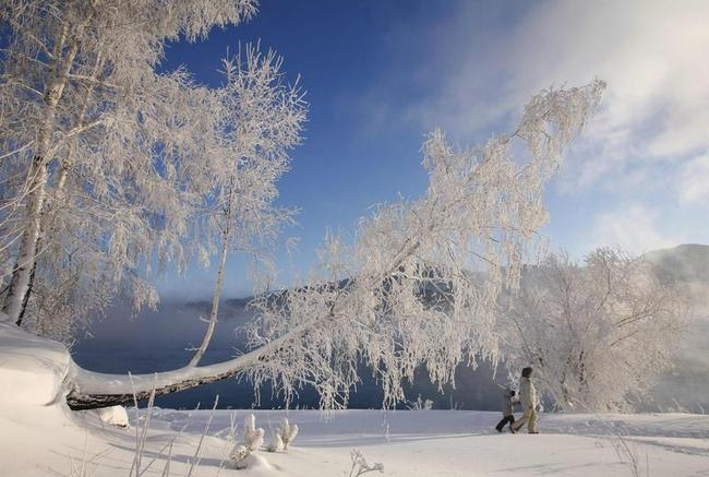A woman walks with her child on the banks of the Yenisey River during winter outside Krasnoyarsk
