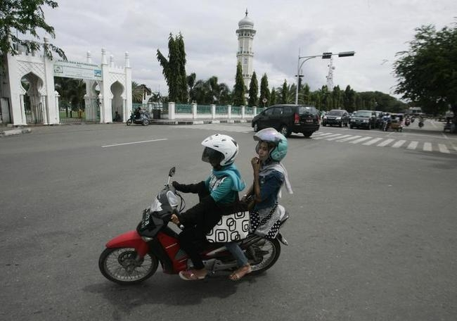 Acehnese women sit straddling on their motorcycles near Baiturrahman mosque in Banda Aceh, Indonesia's Aceh province