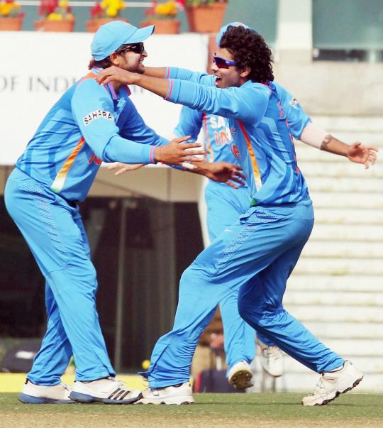 India's R Jadeja celebrates with Suresh Raina and Virat Kohli after dismissing England batsman C. Kieswetter during the 3rd ODI cricket match at JSCA Stadium in Ranchi on Saturday