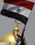 A supporter of deposed Egyptian President Mohamed Mursi shouts slogans in front of army soldiers at Republican Guard headquarters in Nasr City
