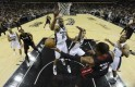 Miami Heat shooting guard Wade passes off under the hoop as he is guarded by San Antonio Spurs' Duncan, Green and Leonard during Game 5 of their NBA Finals basketball series in San Antonio
