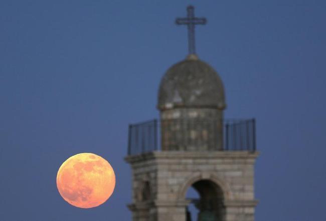 The moon rises behind the Mar Elias Greek Orthodox Monastery in Jerusalem