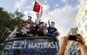Anti-government protesters pose for a souvenir photo on top of a damaged public bus at Taksim square in Istanbul