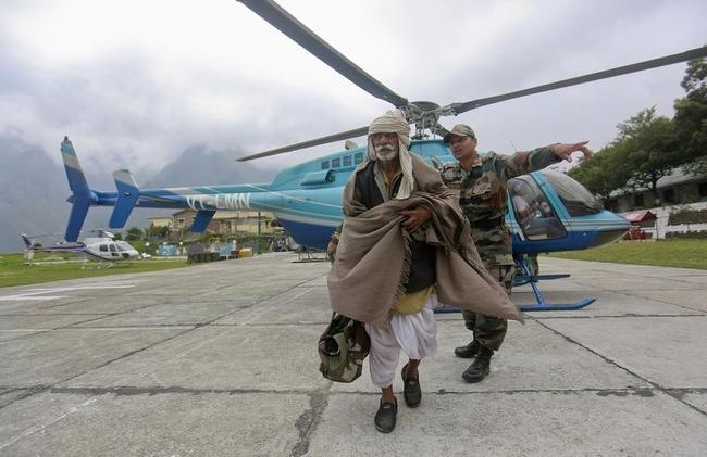 A man is guided by a soldier during a rescue operation at Joshimath in the Himalayan state of Uttarakhand
