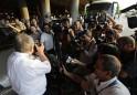 A crew member of Aeroflot's SU150 Moscow-Havana flight takes pictures of reporters at Havana's Jose Marti International Airport